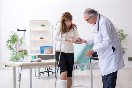 Young injured woman visiting experienced doctor traumatologist
