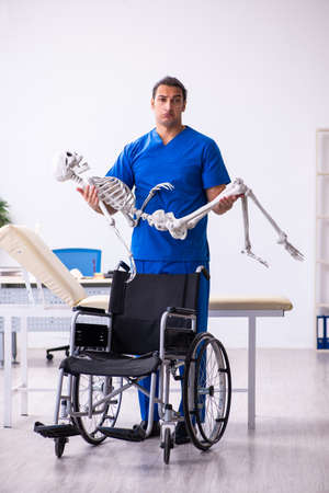 Young male doctor and skeleton in wheel-chair 免版税图像