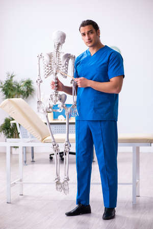 Young male doctor lecturer demonstrating skeleton 免版税图像