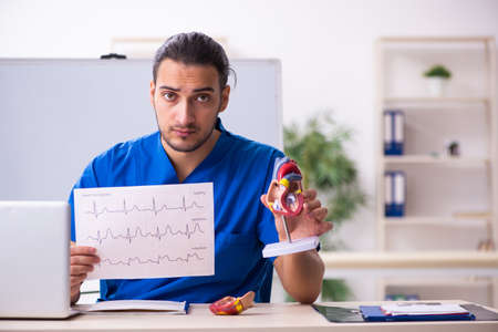 Young male doctor teacher cardiologist in front of whiteboard 免版税图像