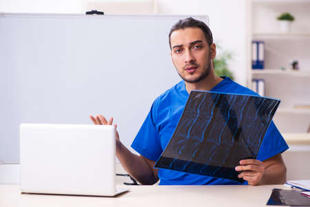 Young male doctor teacher radiologist in front of whiteboard