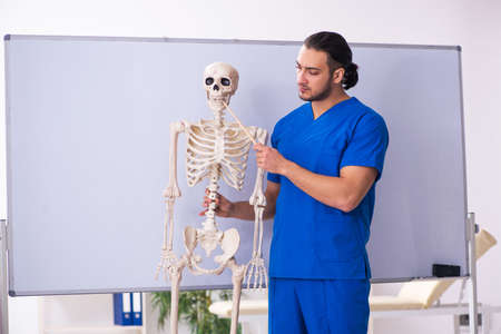 Young male lecturer with skeleton in front of whiteboard