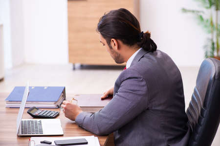 Young male employee reading book in the office