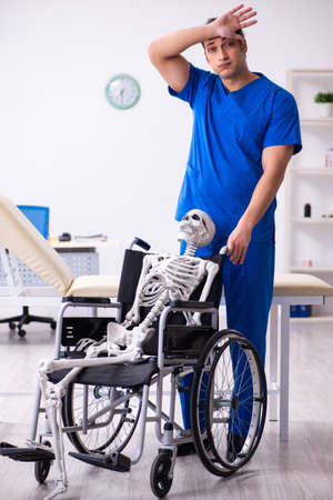Young male doctor and skeleton in wheel-chair Stock fotó