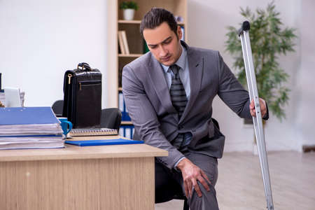 Young leg injured male employee working in the office