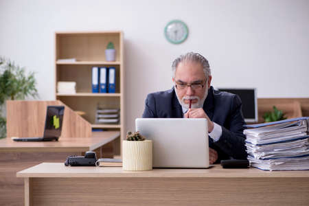 Old male employee working in the office Banco de Imagens