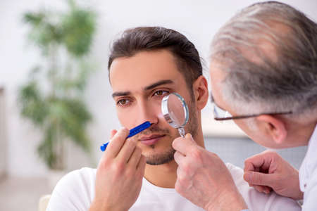 Young man visiting experienced doctor dermatologist Banque d'images