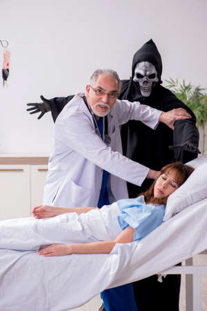 Devil, old doctor and female patient in the clinic 写真素材