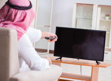 Arab businessman watching tv at home