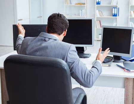 Businessman sitting in front of many screens Foto de archivo