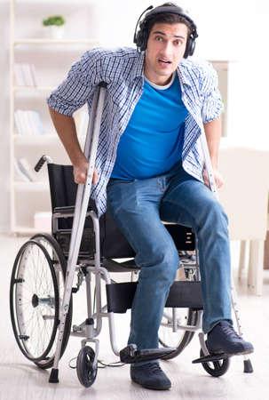 Disabled man listening to music in wheelchair Foto de archivo
