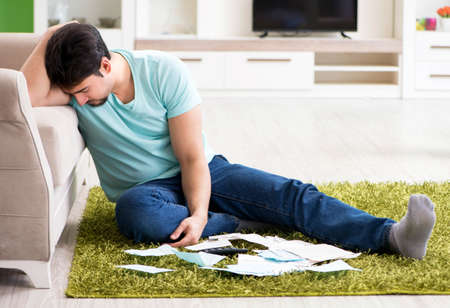 Young man struggling with personal finance and bills Archivio Fotografico
