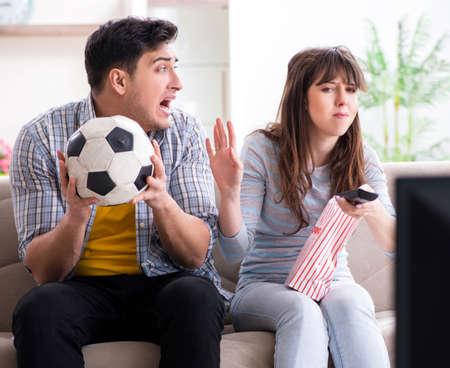 Family pair watching football at home