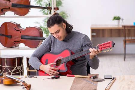 Young male repairman repairing guitar