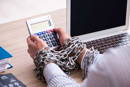 Chained male employee working in the office Imagens