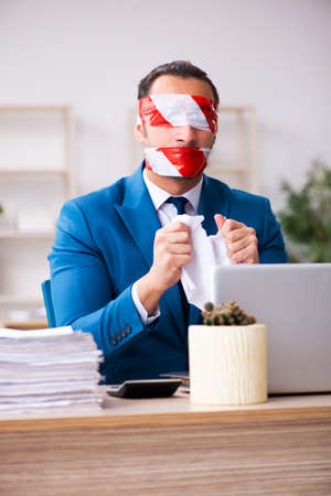 Mouth and eyes closed male employee working in the office Stockfoto