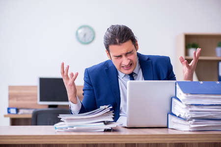 Young male employee unhappy with excessive work Standard-Bild