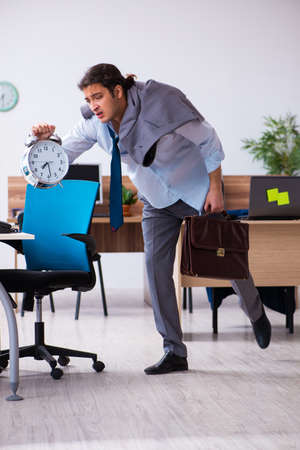 Young male employee being late for his job Standard-Bild