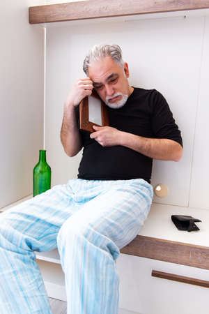Old man drinking wine in the bedroom