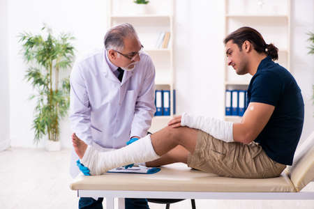 Young injured man visiting old doctor traumatologist Stockfoto