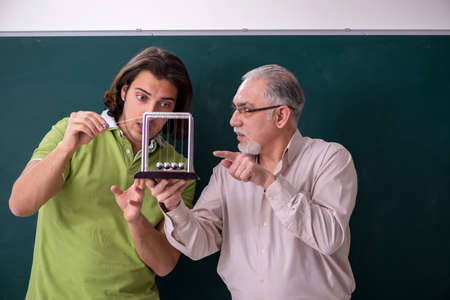 Old professor physicist and young student in the classroom