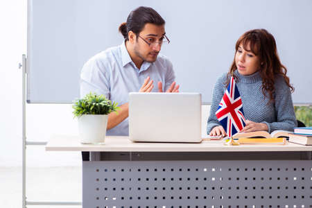 Young female student and male english teacher in the classroom 版權商用圖片