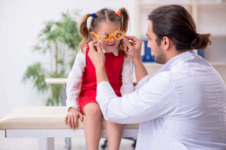 Small girl visiting young male doctor oculist Imagens