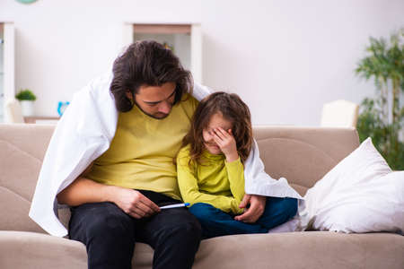 Small girl looking after her sick father Stock Photo