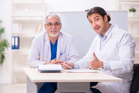 Experienced doctor teaching young male assistant 版權商用圖片