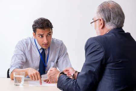 Old businessman meeting with advocate in pre-trial detention Stock Photo