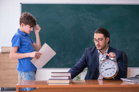 Young male teacher and schoolboy in the classroom