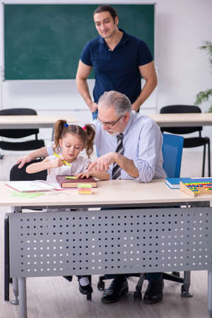 Young parent, old male teacher and little girl in the classroom