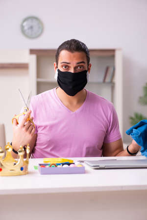 Young male tailor sewing masks at home during pandemic