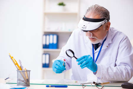 Old male expert criminologist working in the lab for evidence