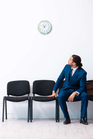 Young businessman waiting for an interview at hall