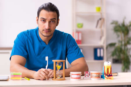Young male dentist working in the clinic