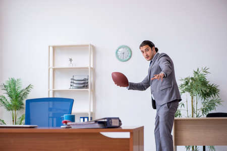 Young male employee with rugby ball in the office