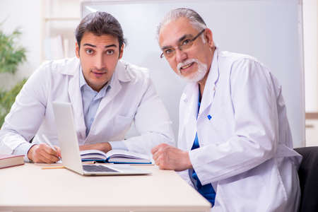 Experienced doctor teaching young male assistant Stockfoto