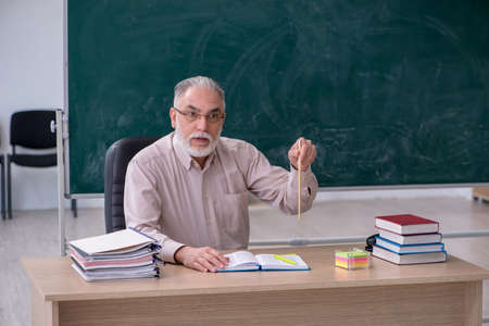 Old male teacher sitting in the classroom