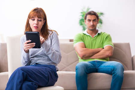 Young couple in gadget dependency concept