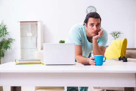 Young male parent looking after newborn at home