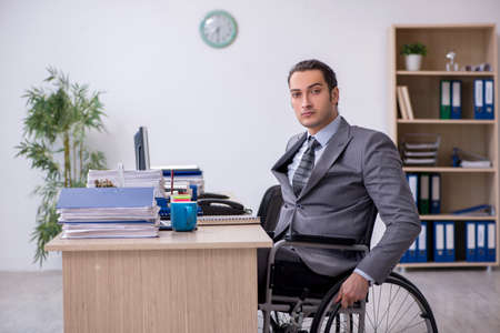 Young male enployee in wheel-chair at workplace