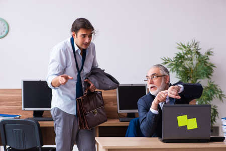 Old boss and his male secretary employee in time management conc Stock Photo