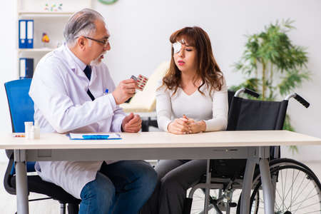 Young woman visiting old male doctor ophthalmologist Standard-Bild