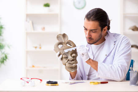 Young male archaeologist studying ancient african stonemask