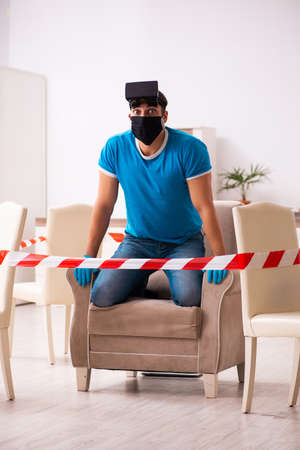Young man enjoying virtual glasses at home during pandemic Stok Fotoğraf