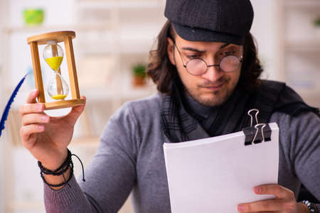 Young male writer in time management concept Stock Photo