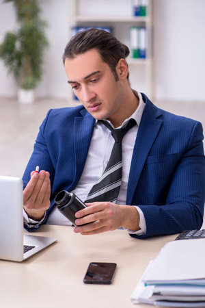 Sick male employee suffering at workplace