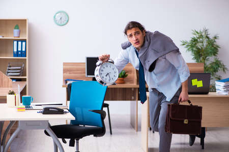 Young male employee being late for his job Archivio Fotografico