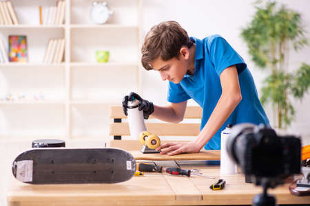 Boy repairing skateboard and recording video for his blog